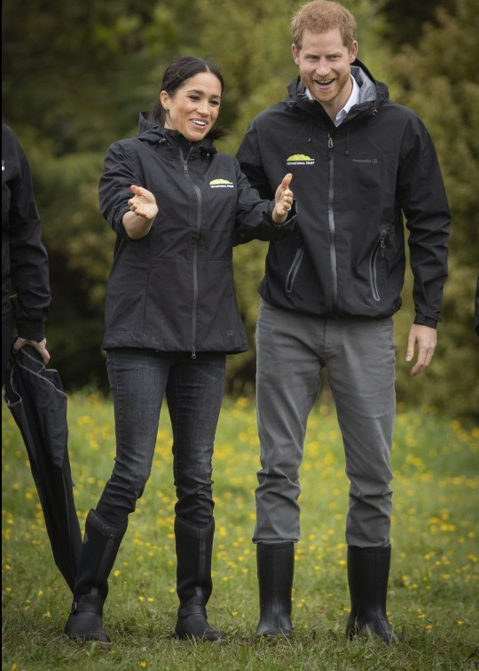 AUCKLAND, NEW ZEALAND - OCTOBER 30: Prince Harry, Duke of Sussex and Meghan, Duchess of Sussex share a laugh after the Gumboot throwing competition after unveiling a plaque dedicating 20 hectares of native bush to the Queen's Commonwealth Canopy project at The North Shore Riding Club on October 30, 2018 in Auckland, New Zealand. The Duke and Duchess of Sussex are on their official 16-day Autumn tour visiting cities in Australia, Fiji, Tonga and New Zealand. (Photo by Greg Bowker/New Zealand Herald - Pool/Getty Images)