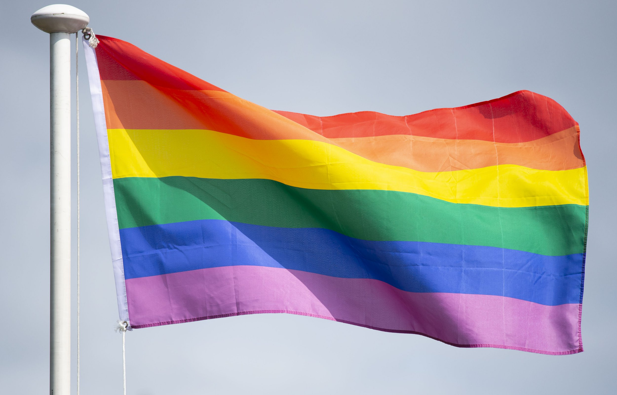 CARDIFF, WALES - AUGUST 25: An LGBT rainbow flag seen during the Pride Cymru parade on August 25, 2018 in Cardiff, Wales. Pride Cymru aims to eliminate discrimination on the grounds of sexual orientation and gender and promote LGBT equality and diversity within Wales. (Photo by Matthew Horwood/Getty Images)