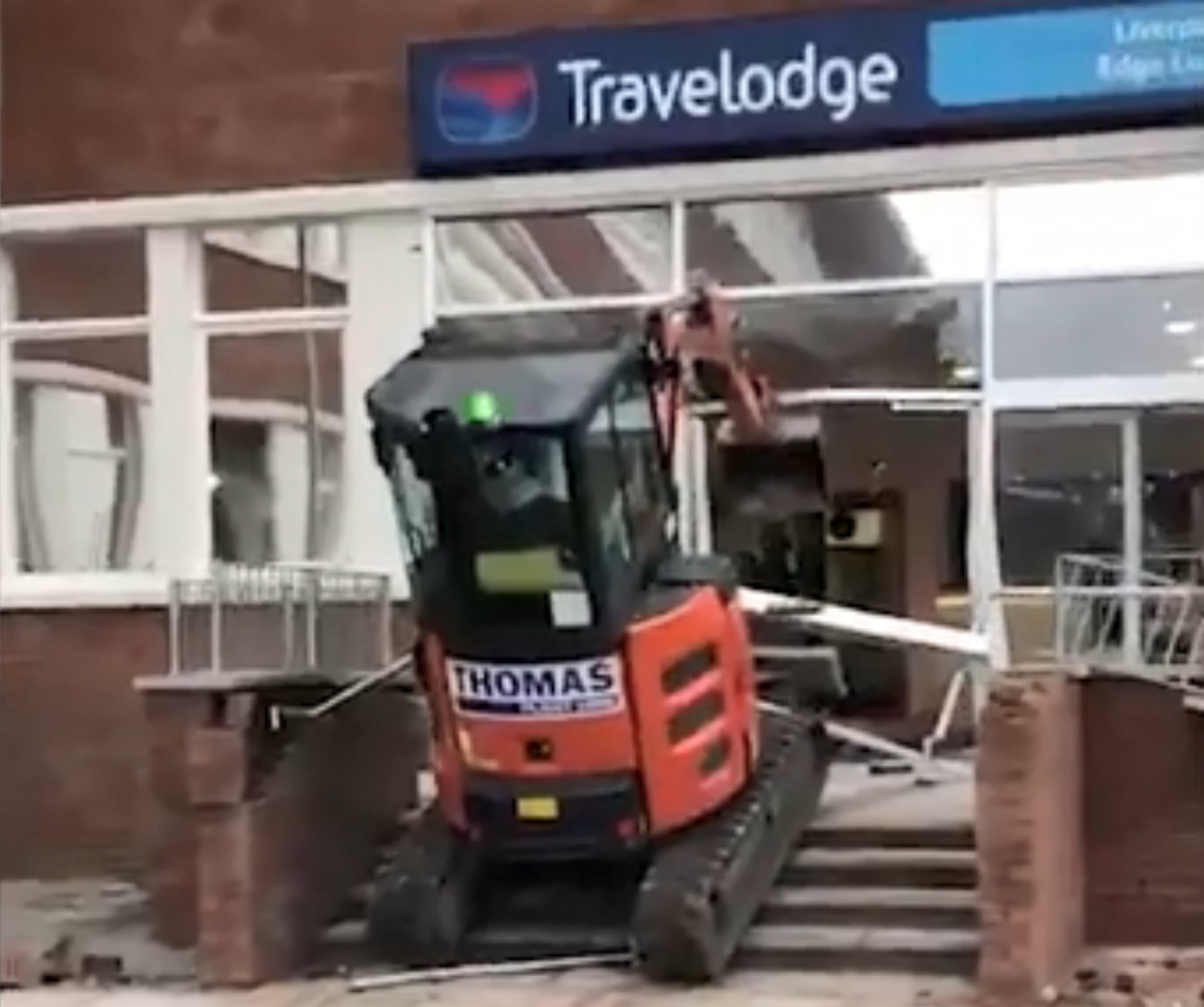 This unbelievable footage shows the bizarre moment a digger driver ploughed into a new hotel building during a bizarre rampage. The video was captured shortly before 3pm today when the plant vehicle can be seen mounting the steps in front of the hotel at Liverpool Innovation Park on Edge Lane. After reaching the top of the steps, the arm of the digger is sent crashing through the glass at the top of the door before tearing through the entrance. A few moments later, the digger rolls back out of the entrance and down the steps but the determined operator heads back up and through the front door. Once inside the reception of the hotel, the digger then proceeds to crash into walls and the front desk. A number of workers can be seen cheering on the driver while videoing the incident on their phones - others appear to be trying to stop him. Images Liverpool Echo