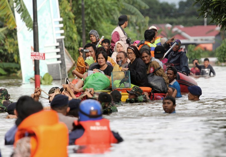 Residents ride a makeshift raft as they evacuate their flooded homes in Makassar, South Sulawesi, Indonesia, Wednesday, Jan. 23, 2019. Torrential rains that overwhelmed a dam and caused landslides that killed some and displaced more than a few thousand residents in central Indonesia, officials said Wednesday. (AP Photo/Masyudi Syachban Firmansyah)
