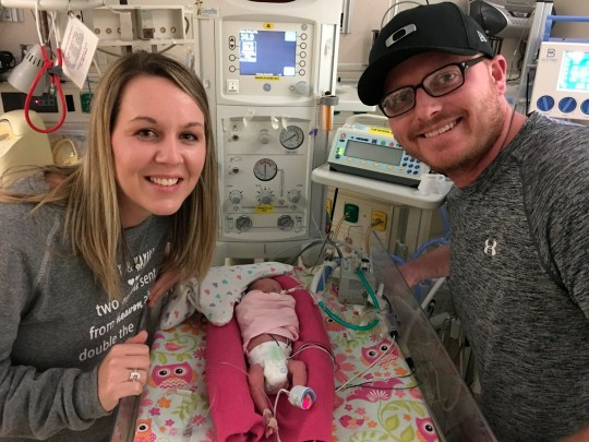 In this Jan. 10, 2019 photo, Jade and Wesley Ewoldt, of Dysart, Iowa, pose with Keeley, one of their twin daughters, in an isolation room at the University of Iowa Hospitals and Clinics in Iowa City, Iowa. The identical twins, Kambry and Keeley, were born 18 weeks premature. (Meta Hemenway-Forbes/The Courier via AP)