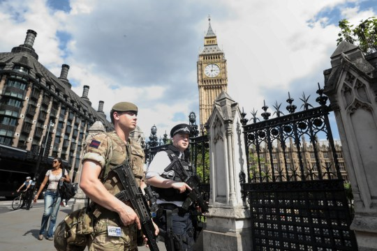 """A soldier and an armed police officer patrol near the Elizabeth Tower, also known as Big Ben, in London, U.K., on Wednesday, May 24, 2017. Soldiers were on patrol at the U.K. Parliament and prepared to guard major sporting events, as authorities rolled out the biggest homeland deployment of troops in decades to prevent an """"imminent"""" terrorist attack. Photographer: Simon Dawson/Bloomberg via Getty Images"""