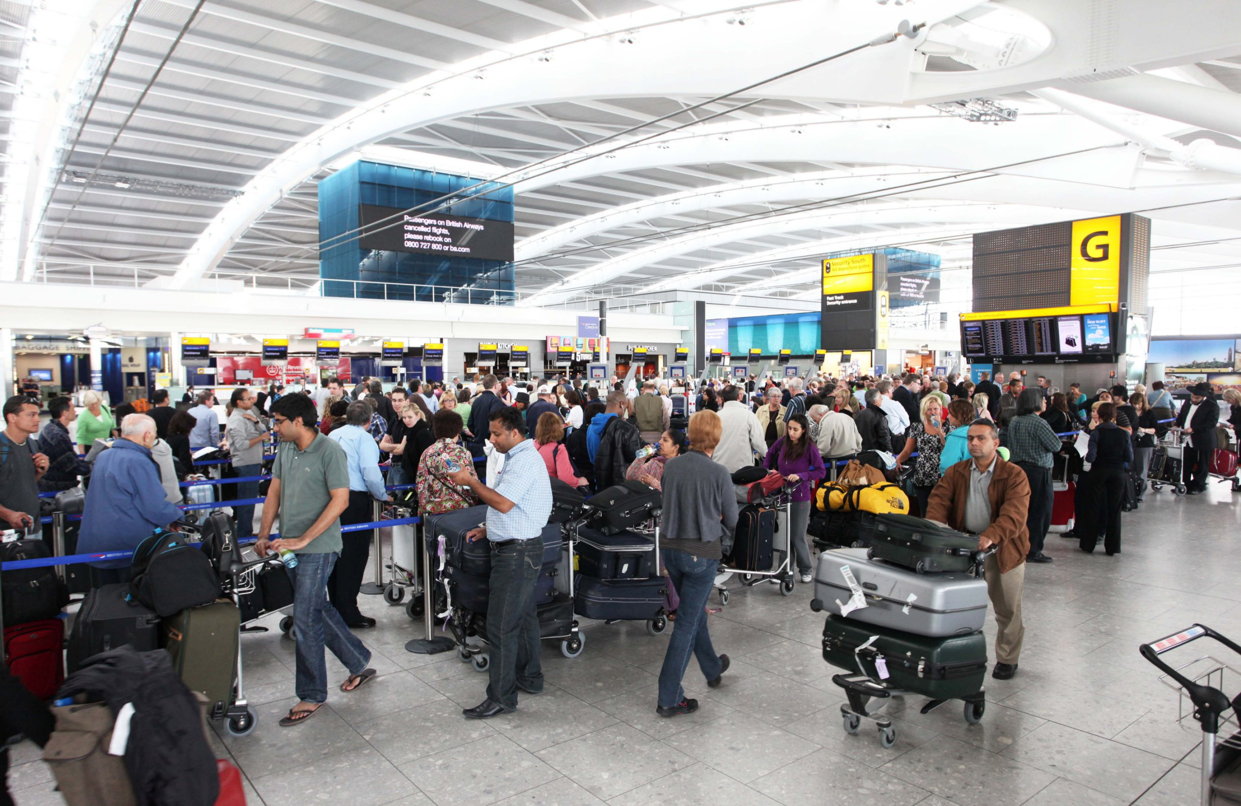 Passengers line up for information at Terminal 5 at Heathrow Airport in London, U.K., on Thursday, April 15, 2010. Airports in the U.K. and northern Europe shut down as a cloud of volcanic ash swept south from an eruption in Iceland, disrupting travel for thousands of people booked on flights with British Airways Plc and other carriers. Photographer: Chris Ratcliffe/Bloomberg via Getty Images
