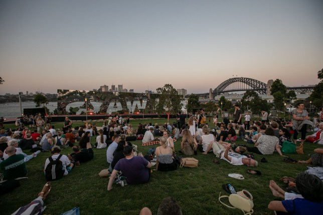 People at the Sydney Festival sit, chill, eat and drink on the grass by the water