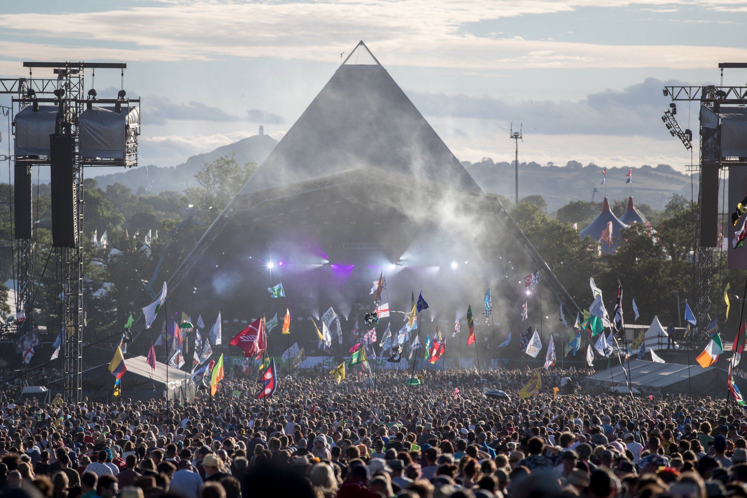 GLASTONBURY, ENGLAND - JUNE 25: People gather in front of the Pyramid Stage at Worthy Farm in Pilton on June 25, 2017 near Glastonbury, England. Glastonbury Festival of Contemporary Performing Arts is the largest greenfield festival in the world. It was started by Michael Eavis in 1970 when several hundred hippies paid just ??1, and now attracts more than 175,000 people (Photo by Matt Cardy/Getty Images)