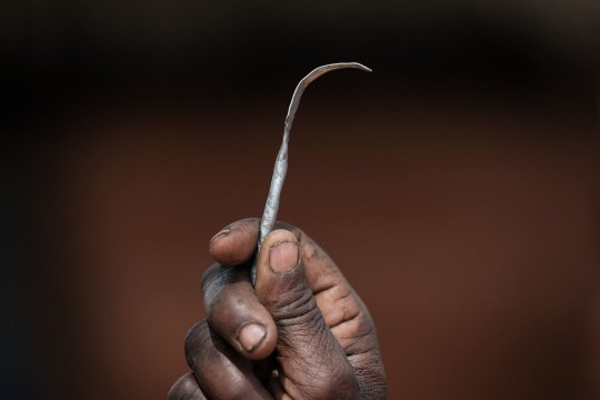 Ex-female genital mutilation (FGM) cutter Monika Cheptilak, who stopped practicing after the country set anti-FGM law in 2010, shows a homemade tool from a nail used for FGM, during the meeting of anti-FGM women group in Alakas village, bordering with Kenya, northeast Uganda on January 31, 2018. The UN estimates that over 200 million girls and women have experienced FGM which is a life-threatening procedure that involves the partial or total removal of a woman's external genitalia. February 6, 2018, marks the 6th International Day of Zero Tolerance for FGM. / AFP PHOTO / Yasuyoshi CHIBA (Photo credit should read YASUYOSHI CHIBA/AFP/Getty Images)