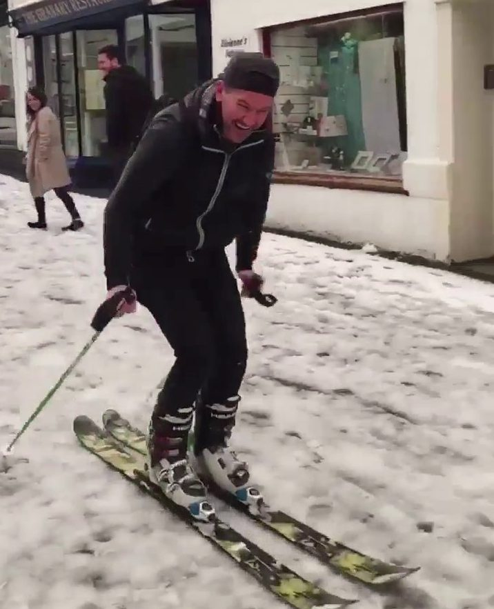 """This incredible videograb shows the moment a man was filmed skiing down a snow-covered street in Cornwall. See SWNS story SWPLski; As the snow fell on Thursday bringing widespread disruption and travel chaos, Olly Danning, 34, decided to unpack his ski gear and head for the highest point he could find. He strapped himself in and put in some perfect parallel turns as he gracefully carved the streets of Wadebridge, Cornwall. Olly said the conditions were perfect for skiing, adding: """"It wasn?t quite the alps but it was good enough."""