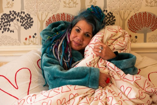 """Pascale Sellick from Exeter, Devon, with her duvet which she plans to marry next month. See SWNS story SWPLduvet; A woman who plans to marry her duvet has revealed she got cold feet after becoming known as the 'duvet lady'. Pascale Sellick, 49, went viral last month when she announced plans to marry her duvet, as it was the """"most intimate and reliable relationship"""" she had ever had. But the artist, from Exeter, Devon, was shocked by becoming an internet celebrity and now has doubts about the unusual ceremony. But for now plans are still going ahead, and Pascale and her duvet are due to be wed on Sunday, February 10, at 2pm."""