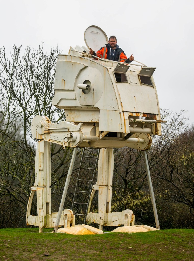 Paul Parker with his full-sized model of an Imperial scout walker at his farm near Ashburton, Devon. See SWNS story SWSTARWARS; A Star Wars fan has been granted retrospective planning permission for a ??12,000 full-size Scout Walker installed beside the A38 - ending a battle with his local council. Paul Parker installed the life-size figure of an AT-ST, which featured in Return of the Jedi, in his field near Ashburton, Devon. It won the hearts of locals and Highways England said it was not a distraction to passing motorists after Teignbridge District Council gave Paul 21 days to take it down. But the statue, erected in November, has been approved and can remain on its spot for the next ten years.