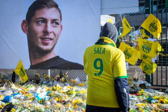 Supporters pay tribute and look at yellow flowers displayed in front of the portrait of Argentinian forward Emiliano Sala at the Beaujoire stadium in Nantes, on February 10, 2019. - FC Nantes football club announced on February 8, 2019 that it will freeze the #9 jersey as a tribute to Cardiff City and former Nantes footballer Emiliano Sala who died in a plane crash in the English Channel on January 21, 2019. (Photo by LOIC VENANCE / AFP)LOIC VENANCE/AFP/Getty Images