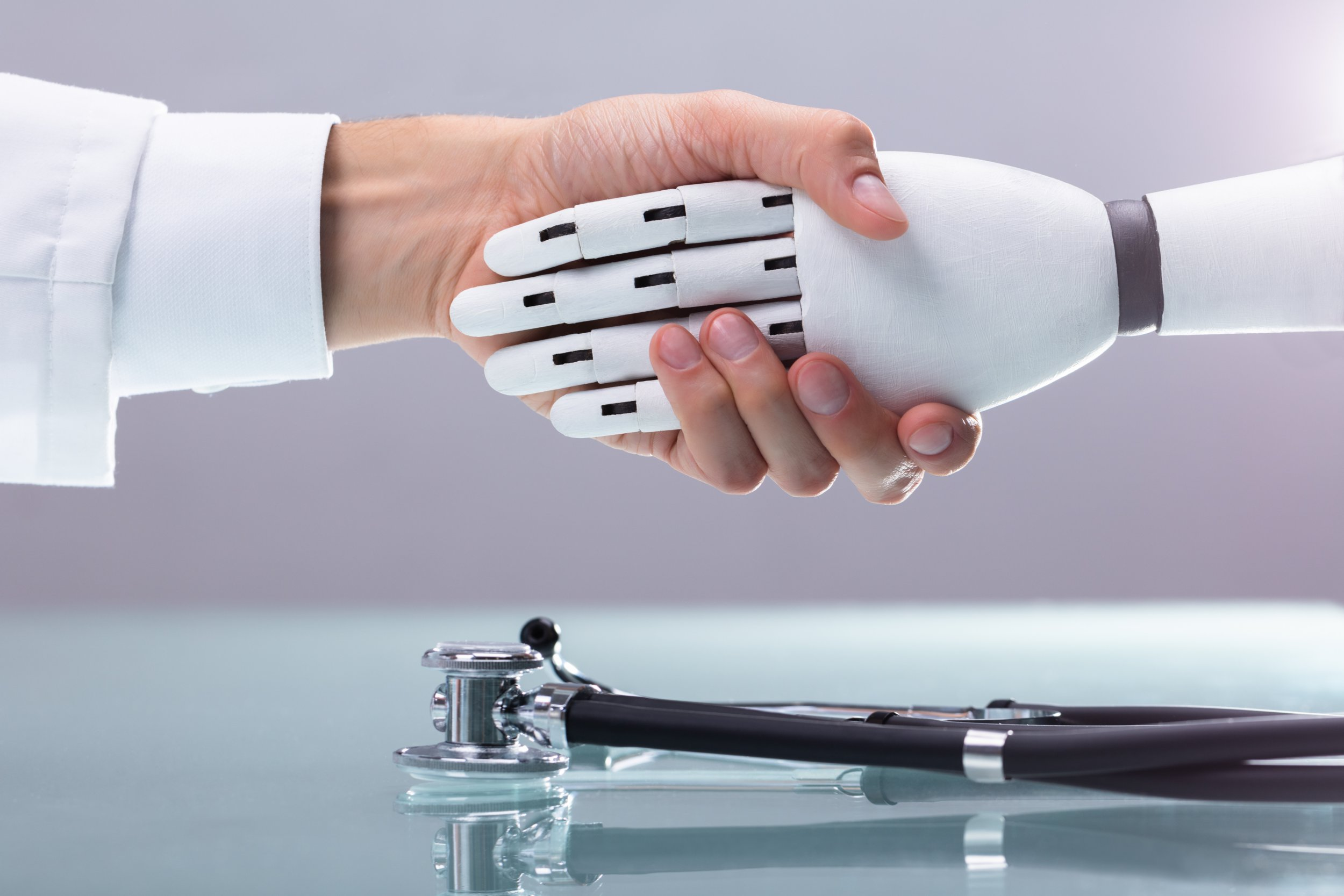 Doctor And Robot Shaking Hands Over Stethoscope