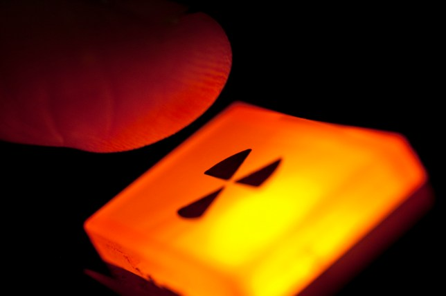 Finger hovering over an illuminated radiation warning sign - or the nuclear option (...or a piece of laboratory equipment actually).