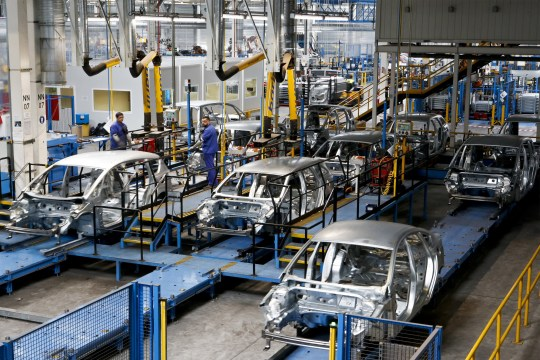 Employees watch as automobile bodies pass by the automated assembly line at the Ford Motor Co. plant in Almusafes, Spain, on Monday, April 18, 2016. Ford's Valencia plant is one of the most advanced, flexible and productive auto plants in the world according to a company statement. Photographer: Pau Barrena/Bloomberg via Getty Images