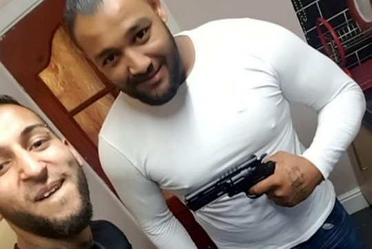 Norbert Pulko (L) and Jan Dudi holding the gun said to have been used to scare Adam Cech into carrying out the acid attack. See SWNS story SWMDacid. This is the moment alleged conspirators grinned as they posed with a 'gun' said to have been used to 'scare' a man into squirting acid on a three-year-old boy in Worcester. The photo shows alleged conspirators Norbert Pulko and Jan Dudi posing with the BB gun the day before sulphuric acid was sprayed on the boy in Home Bargains, Worcester. The images were shown to a jury during the acid attack conspiracy trial at Worcester Crown Court today. Six men and a woman deny conspiracy to apply a corrosive fluid with intent to burn, maim, disable or disfigure the boy or do him grievous bodily harm. Adam Cech claims this same 'gun' was used by Pulko to threaten him into squirting the boy on Saturday, July 21 last year at 2.16pm.