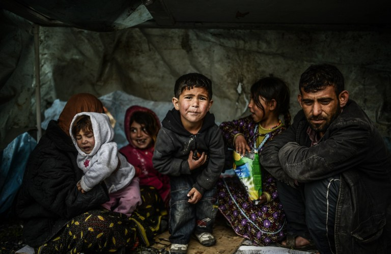 A Syrian refugee family from Aleppo, stay under a shelter during a rainy day on March 8, 2014, at Uskudar in Istanbul. More than 136,000 people have been killed in Syria's brutal war since March 2011, and millions more have fled their homes. AFP PHOTO/BULENT KILIC (Photo credit should read BULENT KILIC/AFP/Getty Images)