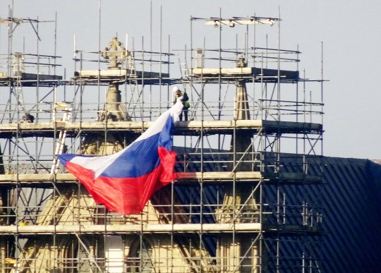 "Pranksters who scaled scaffolding to drape a huge Russian flag on the north front of Salisbury Cathedral were condemned today. See SWNS story SWBRflag. Unknown persons pinned the large blue, white and red flag to the top of scaffolding erected on the Wiltshire landmark overnight on Saturday. This morning workmen were seen removing it from its lofty post. The stunt on the landmark in the city at the centre of the 'novichok' nerve agent poisonings was quickly condemned. Salisbury's MP John Glen tweeted;""What a stupid stunt - mocking the serious events sadly experienced in Salisbury last year."" The city hit the headlines last year when former Russian spy Sergei Skripal and his daughter Yulia were found unwell, after having been exposed to the nerve agent novichok. Salisbury police officer DS Nick Bailey was also left seriously ill after coming into contact with it at the Skripal's house."