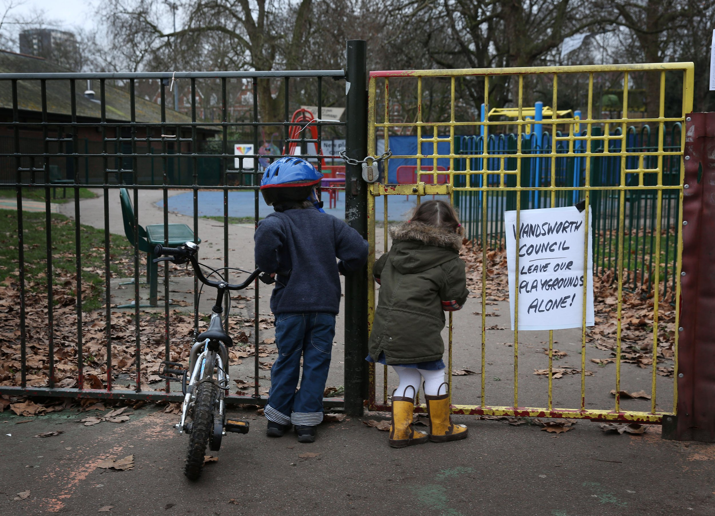 British children are more likely to be obese, in poverty and sick than those in other countries LONDON, ENGLAND - JANUARY 08: Children look into a closed playground next to Battersea Park adventure playground on January 8, 2013 in London, England. Activists and local residents oppose local authority plans to demolish the adventure playground, which has been mostly used by teenagers, and replace it with facilities for younger children who will need less supervision. (Photo by Peter Macdiarmid/Getty Images)