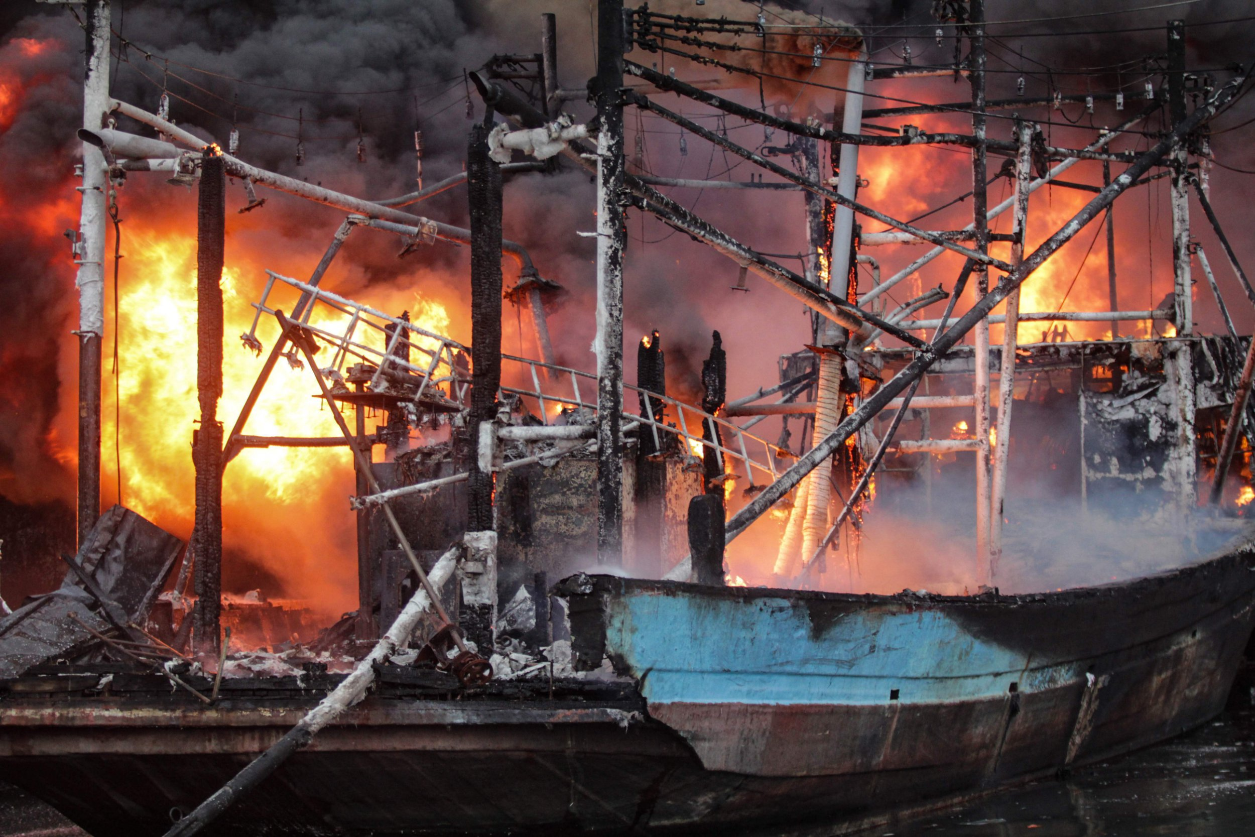 Flames rise from burning wooden boats during a fire at the Muara Baru port in Jakarta on February 23, 2019. (Photo by KRISNADA / AFP)KRISNADA/AFP/Getty Images