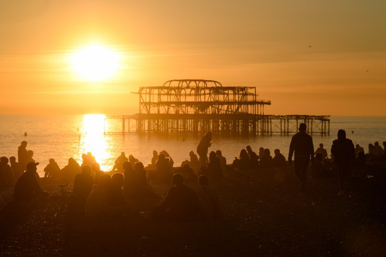 LONDON, ENGLAND - FEBRUARY 25: People enjoy the setting Sun on the beach by the derelict West Pier on February 25, 2019 in Brighton, England. The UK has been experiencing unseasonably mild weather conditions, with the Met Office reporting a temperature of 20.3C (68.54F) at Trawsgoed, Ceredigion. on February 25, 2019 in London, England. (Photo by Mike Hewitt/Getty Images)