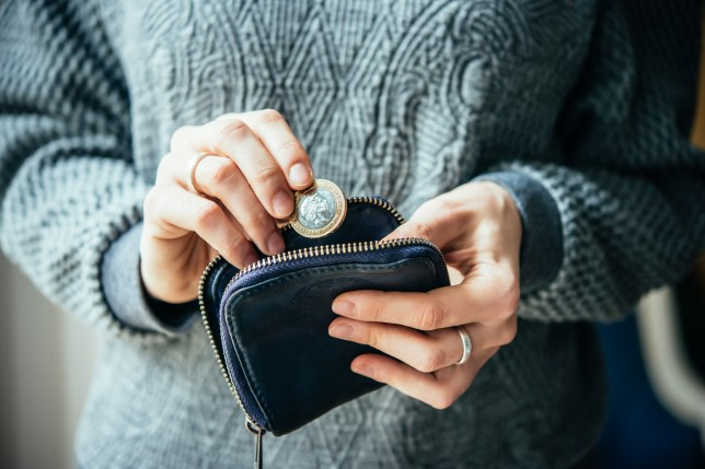 Hands holding british pound coin and small purse