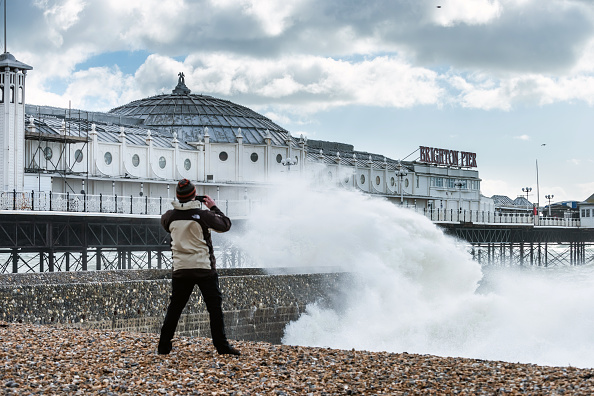 Man standing on Brighton beach taking a picture of the rough sea on his phone, with Brighton Pier in the background.