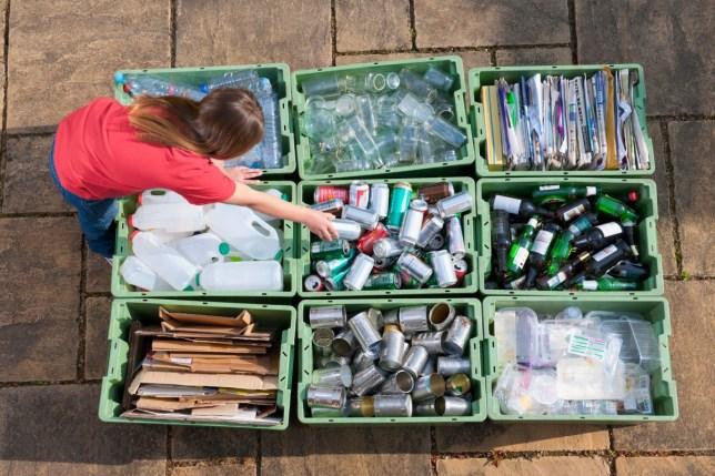 Caucasian teenage girl organizing recycling bins