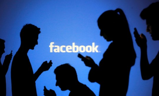 FILE PHOTO: People are silhouetted as they pose with mobile devices in front of a screen projected with a Facebook logo, in this picture illustration taken in Zenica, October 29, 2014. REUTERS/Dado Ruvic/File Photo