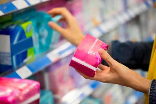 Unrecognizable woman is choosing between pad and tampon in the store, selective focus