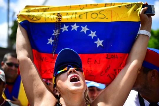 """A supporter of Venezuelan opposition leader and self-proclaimed acting president Juan Guaido holds a Venezuelan national flag reading """"For my children, for my grandchildren"""" as she waits for his return in Caracas on March 4, 2019. - Opposition supporters in Venezuela were set to take to the streets Monday after leader Juan Guaido called for mass protests against President Nicolas Maduro -- as the self-declared interim president prepared to return after a week touring Latin American allies. (Photo by RONALDO SCHEMIDT / AFP)RONALDO SCHEMIDT/AFP/Getty Images"""