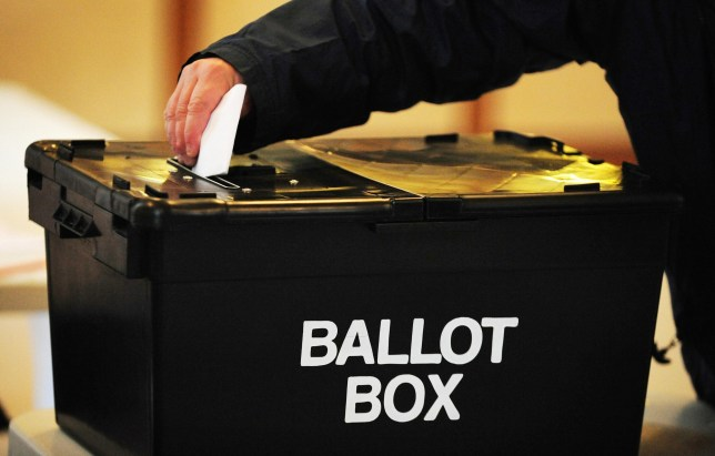 Image of voter putting a piece of paper into a large black ballot box