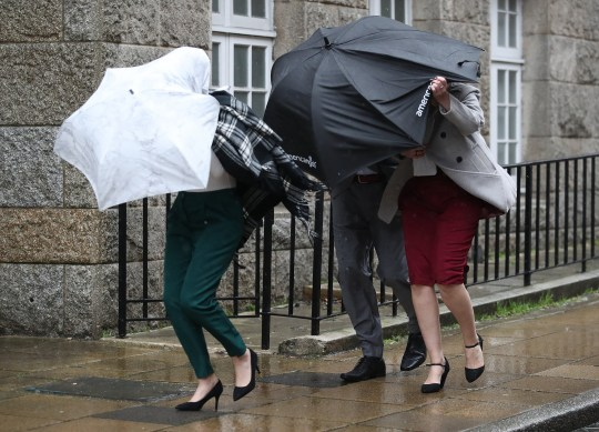 People use umbrellas to shelter from the wind and rain as they make their way along Tower Street in Winchester, Hampshire.