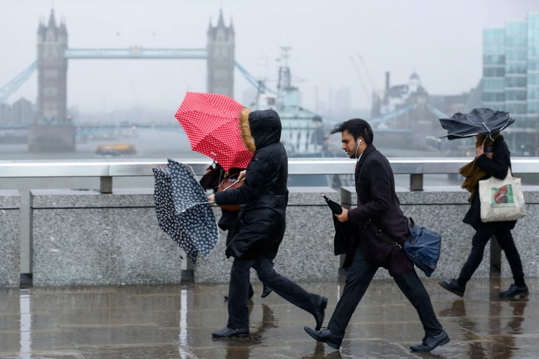 Commuters carrying umbrellas to shelter from the rain battle against high winds as they cross London Bridge during the approach of the 'Storm Doris' weather front in London, U.K., on Thursday, Feb. 23, 2017. The U.K.'s withdrawal from the European Union will be expensive for Britain, Austrian Chancellor Christian Kern said. Photographer: Luke MacGregor/Bloomberg via Getty Images