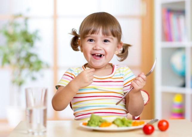 smiling kid girl eating healthy vegetables at kitchen
