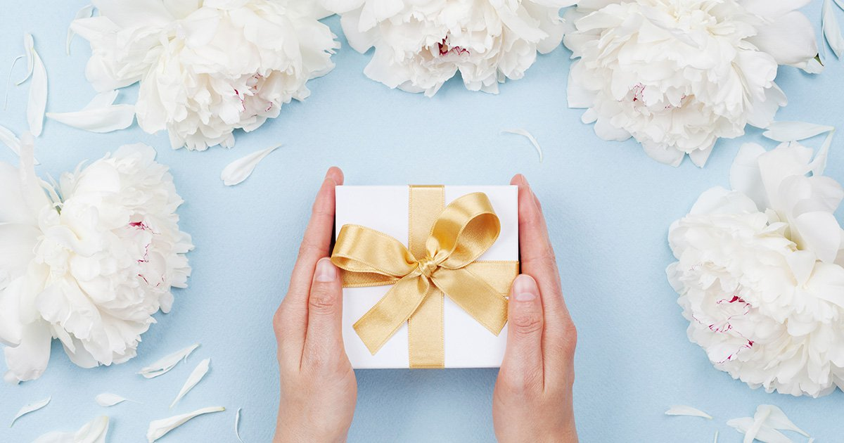Womans hands giving gift or present box decorated white peony flowers on pastel table top view. Flat lay composition for birthday or wedding.