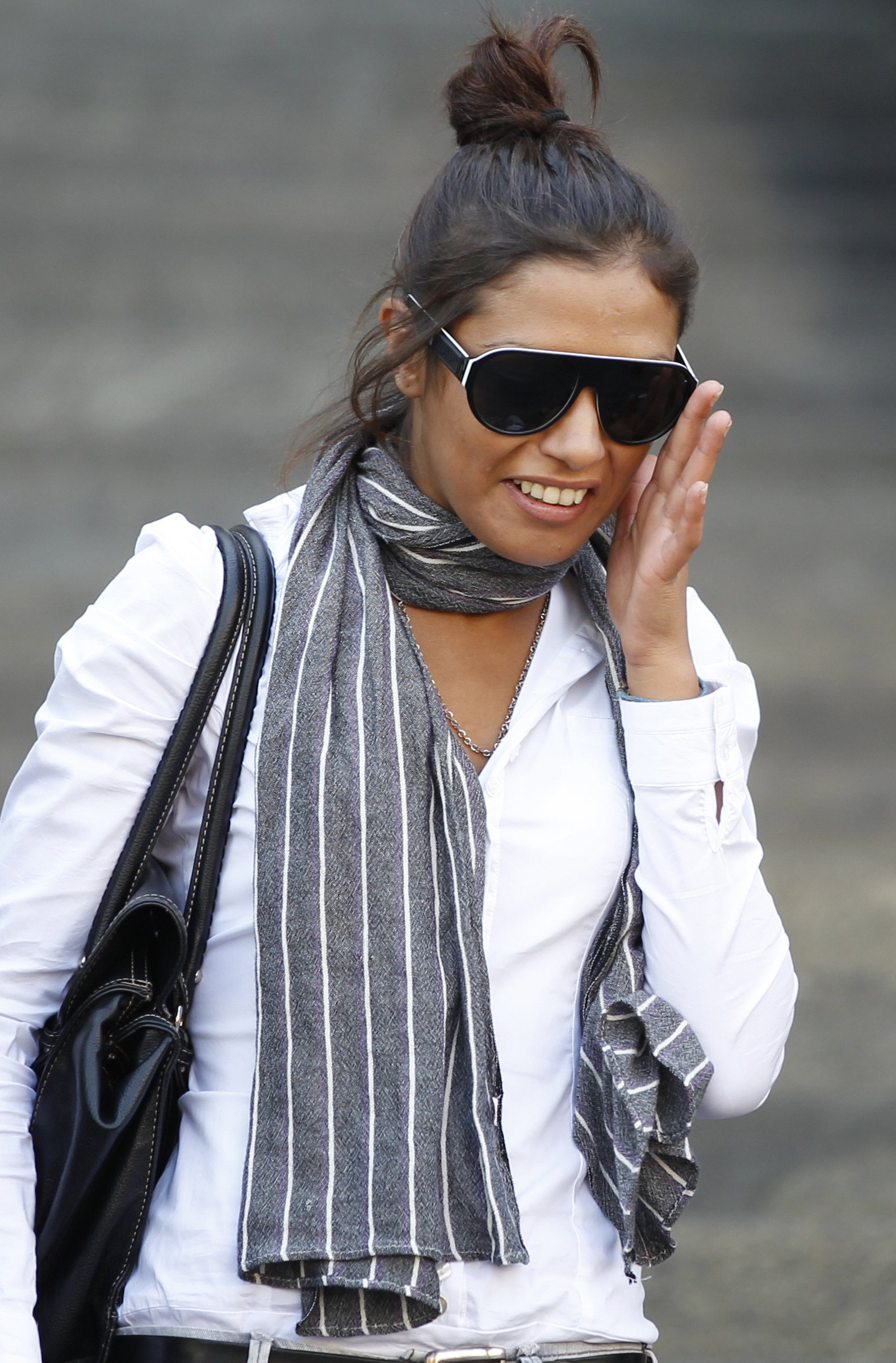 """FILE - In this Monday, Oct. 3, 2011 file photo, Imane Fadil smiles as she leaves the court in Milan, Italy. Italy prosecutors have opened an investigation into the death of a Moroccan model who testified in one of the inquiries linked to ex-Premier Silvio Berlusconi's """"bunga bunga"""" parties. Citing Milan prosecutor Francesco Greco, Italian news agency ANSA reported that Imane Fadil died March 1 at a Milan hospital, where she had been treated since Jan. 29 exhibiting """"symptoms of poisoning."""" (AP Photo/Luca Bruno, File)"""