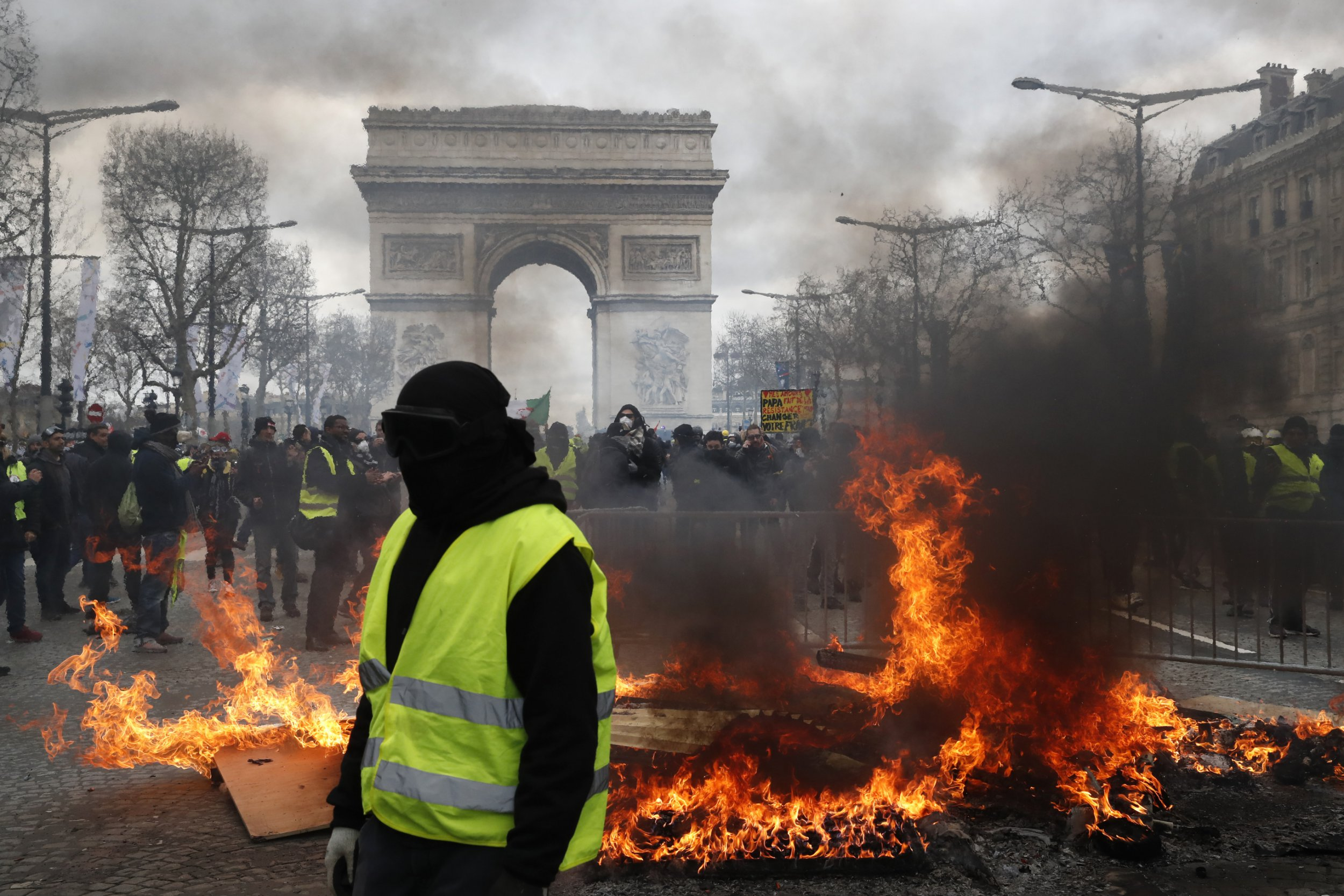 A yellow vest protester walks past a fire on the Champs Elysees avenue Saturday, March 16, 2019 in Paris. French yellow vest protesters clashed Saturday with riot police near the Arc de Triomphe as they kicked off their 18th straight weekend of demonstrations against President Emmanuel Macron. (AP Photo/Christophe Ena)