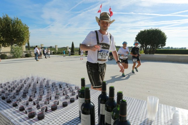 A runner stops of a wine break in the courtyard of Chateau Montrose, near Pauillac, during the 30th Marathon du Medoc, a 26-mile (42.2km) circuit in the Medoc wine region near Bordeaux in south-western France which takes in more than 30 of the regions' chateaux and vineyards, on September 13, 2014. The Medoc region's world-famous chateaux include Chateau Lafite Rothschild, Chateau Mouton Rothschild and Chateau Latour, all open their grounds and cellars to offer runners some of the world's most respected wines at 23 drinks stations along the route, as well as countless food stops serving local delicacies from foie gras, oysters and entrecote steak, to ham, cheese and fruit. AFP PHOTO / NICOLAS TUCAT (Photo credit should read NICOLAS TUCAT/AFP/Getty Images)