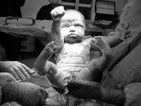 Dad captures his baby son pulling the superhero pose the minute he was born