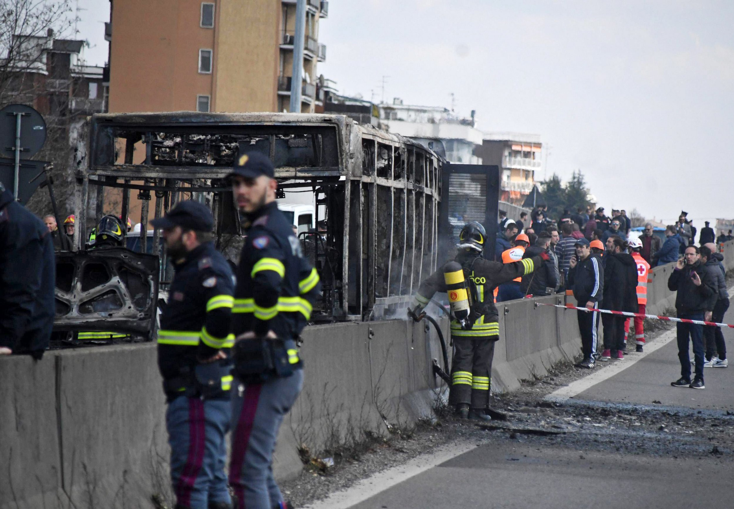 epa07450610 Firefighters and policemen where a bus was set on fire by a driver in Milan, Italy, 20 March 2019. A 47-year-old man was held by Carabinieri police after allegedly hijacking a bus with schoolchildren aboard and subsequently starting a fire inside the vehicle, sources said. According to an initial reconstruction, the man hijacked the bus with 51 pupils of a middle school at Vailati di Crema, in the northern province of Cremona, and said he wanted to kill himself. EPA/DANIELE BENNATI