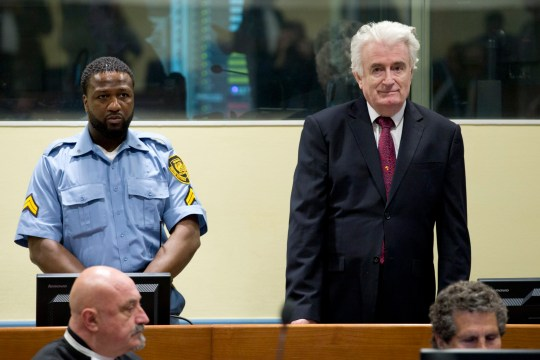 Former Bosnian Serb leader Radovan Karadzic enters the court room of the International Residual Mechanism for Criminal Tribunals in The Hague, Netherlands, Wednesday, March 20, 2019. Nearly a quarter of a century since Bosnia's devastating war ended, Karadzic is set to hear the final judgment on whether he can be held criminally responsible for unleashing a wave of murder and destruction. United Nations appeals judges will on Wednesday rule whether to uphold or overturn Karadzic's 2016 convictions for genocide, crimes against humanity and war crimes, as well as his 40-year sentence. (AP Photo/Peter Dejong, Pool)