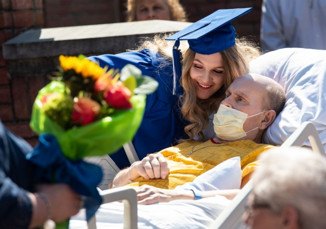 Lindale High School senior Christan Patterson leans in close to her father Mark Patterson at the conclusion of her mock graduation ceremony at Hospice of East Texas in Tyler, Texas on Wednesday March 20, 2019. Being able to see Christan graduate was one of Mark's life goals. Mark has late stage Esophageal cancer. (Sarah A. Miller/Tyler Morning Telegraph via AP)