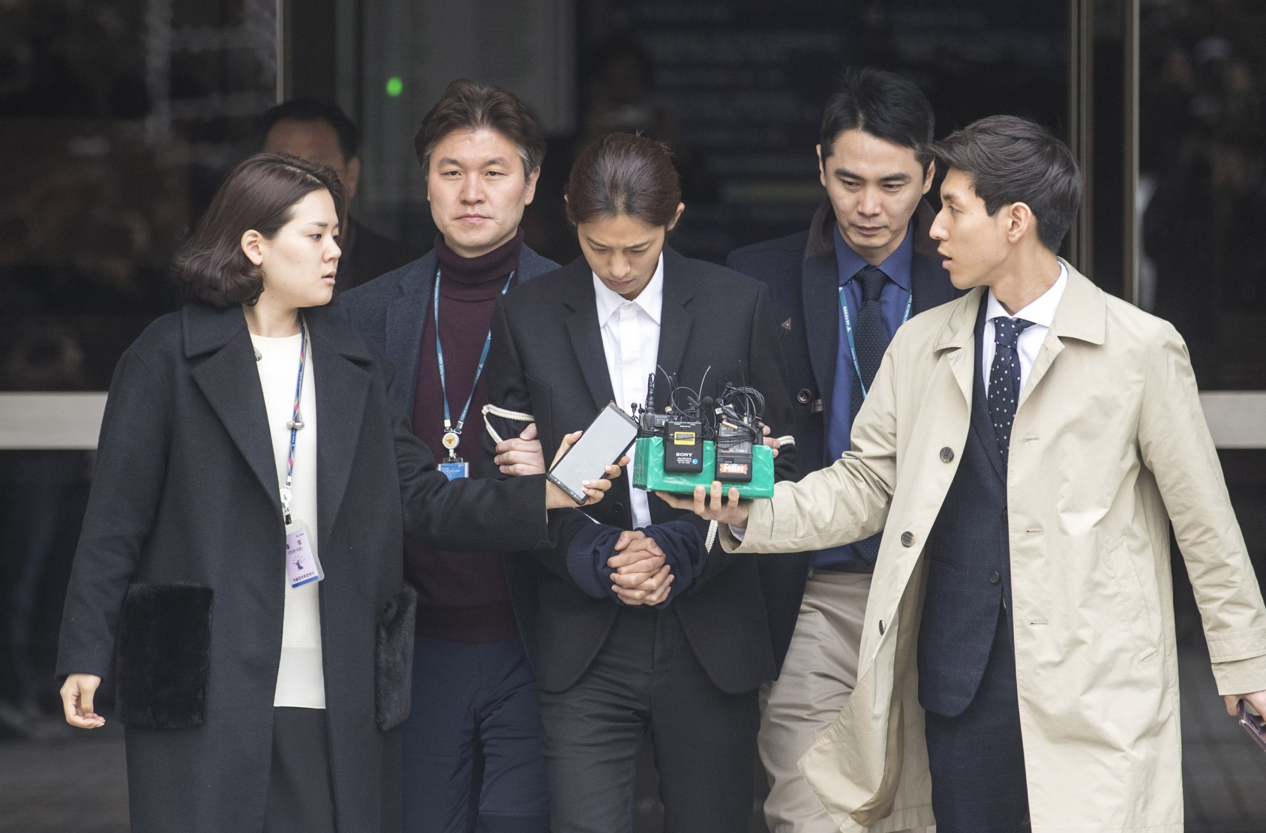 epaselect epa07452192 South Korean K-pop star Jung Joon-young (C), walks with policemen (2-R and 2-L) while waiting of the court's decision at the Seoul District Court in Seoul, South Korea, 21 March 2019. The popstar was at court to attend a hearing after he admitted to secretly filming himself engaging in sexual activities with ten or more women and sharing the footage. EPA/KIM CHUL-SOO