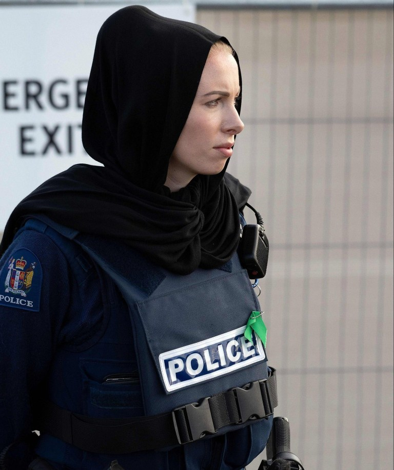 27fa1d0f7d4 A police officer wearing a head scarf stands guard during a funeral  ceremony at the Memorial