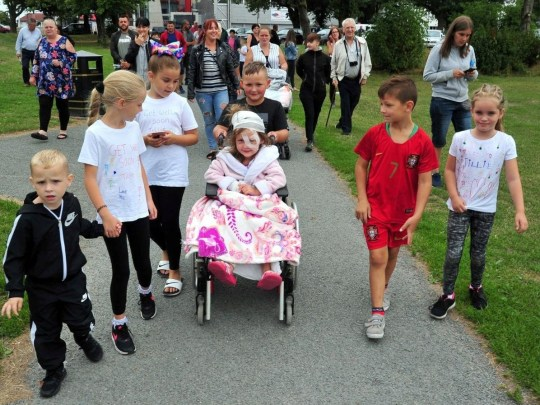 Tillie joined family, friends and neighbours at the start of a sponsored walk around Moor Park, even though she remains under treatment at the Royal Preston nine days after she was saved from the jaws of a pitbull cross. See SWNS story SWLEattack - A judge has slammed the owner of a devil dog which almost mauled a five-year-old girl to death as she played outside -- after she claimed it was the victim's FAULT. 4-year-old Tillie Vasey had 9 hours of surgery after the horrific dog attack in Preston in July 2018