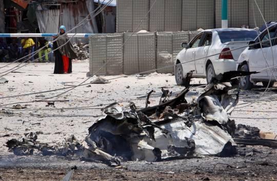 A woman stands behind wreckage left from a suicide car bomb attack on a government building in the capital Mogadishu, Somalia Saturday, March 23, 2019. Al-Shabab gunmen stormed into the government building following a suicide car bombing at the gates on Saturday, a police officer said, in the latest attack by Islamic extremist fighters in the Horn of Africa nation. (AP Photo/Farah Abdi Warsameh)