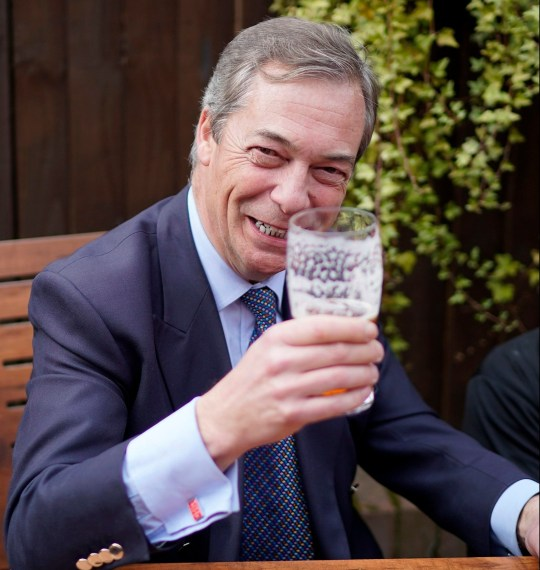"NOTTINGHAM, ENGLAND - MARCH 23: Former UKIP leader Nigel Farage, wears 'Keep Calm and Carry ON"" cufflinks, as he drinks a pint of beer at the Last Post pub at the end of the 'March to Leave' walk from the village of Linby to Beeston, Nottinghamshire on March 23, 2019 in Nottingham, England. The 'March to Leave' walk is making its way to London in 14 stages arriving on March 29, the original date for the UK to leave the European Union. (Photo by Christopher Furlong/Getty Images)"