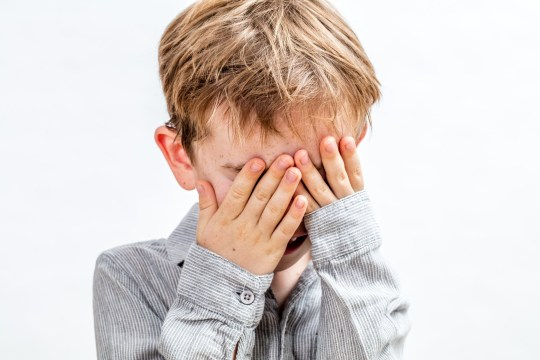 cute little boy covering his face for playing peekaboo, hide and seek, disappearing or being shy over white background, indoors; Shutterstock ID 724409827; Purchase Order: -