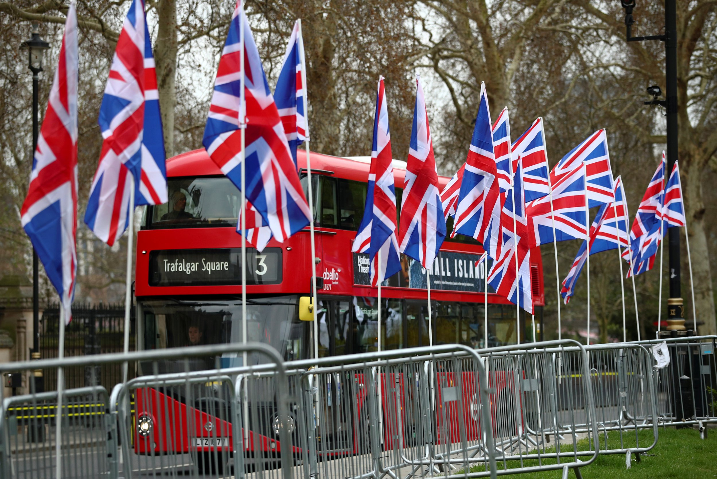 A double-decker bus passes by Union Jack flags displayed by pro-Brexit supporters outside the Houses of Parliament, following the Brexit votes the previous evening, in London, Britain, March 28, 2019. REUTERS/Hannah McKay