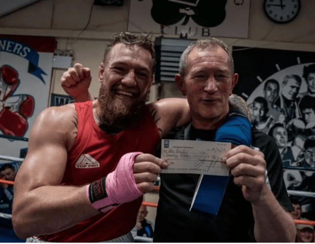 Conor McGregor poses with a cheque for his former boxing coach