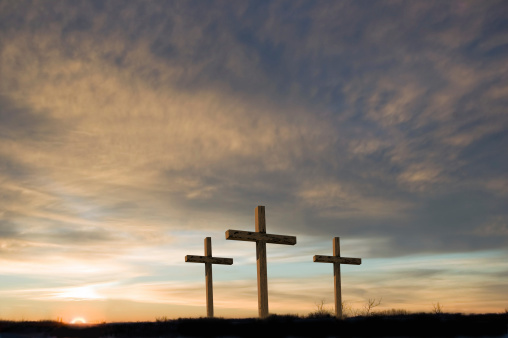 Three crosses in a field with a sunset in the background